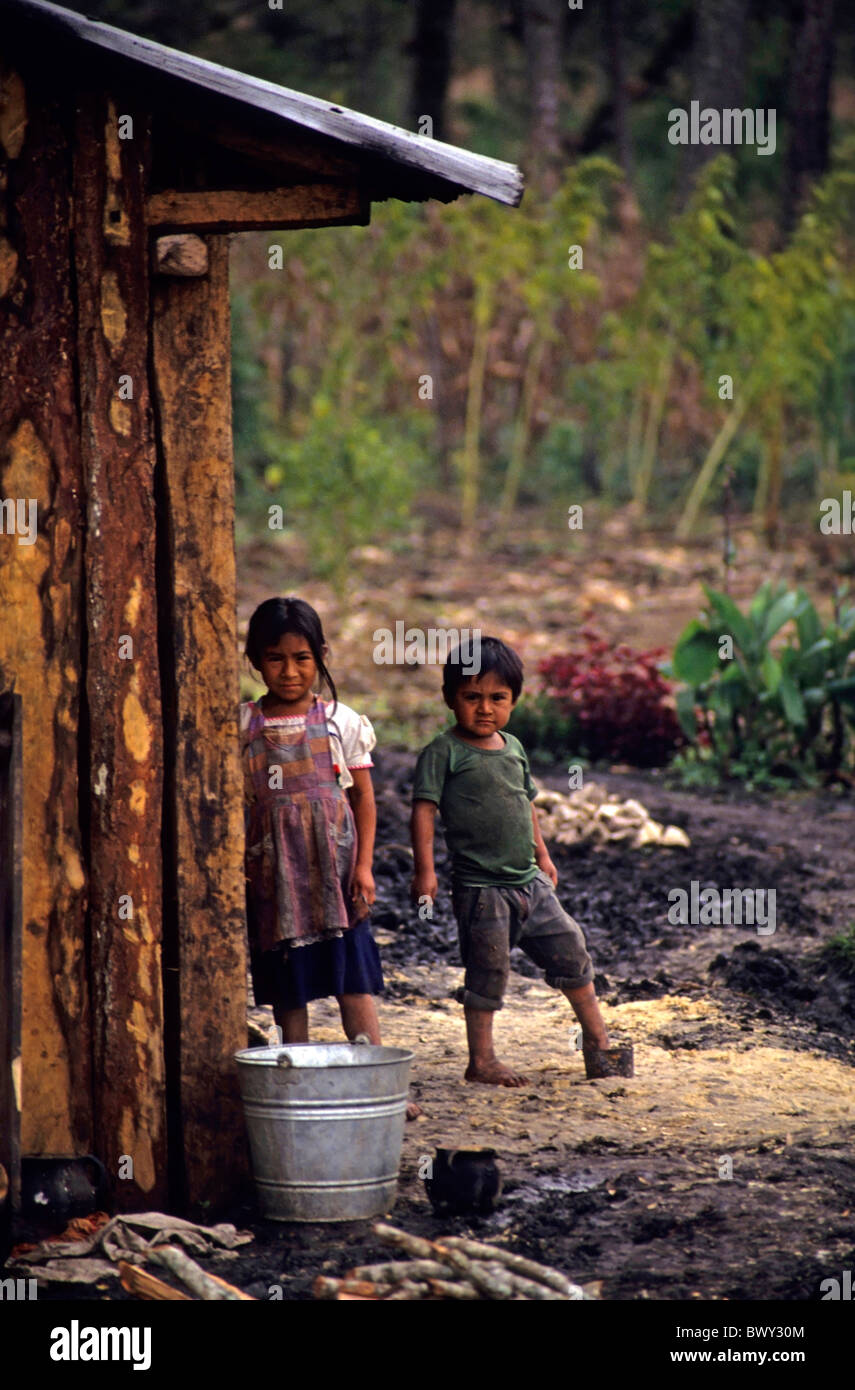 Two Guatemalan children outside a wooden house in a refugee camp near the border, Santa Esmeralda, Chiapas, Mexico. - Stock Image