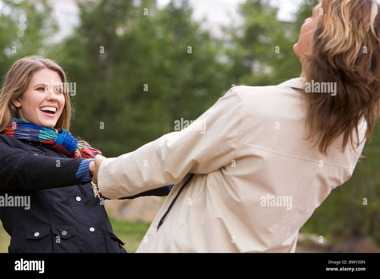 Portrait of affectionate couple whirling outside - Stock Image