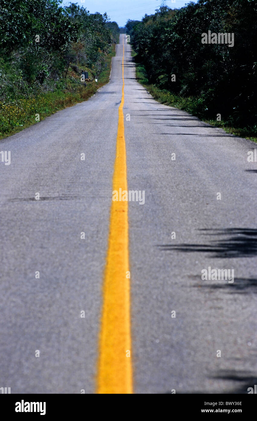 Yellow dividing line marking an empty road between Uxmal and Kabah, Yucatan, Mexico. - Stock Image