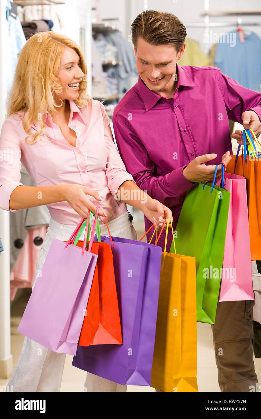 Image of woman showing to man what she bought in the shop - Stock Image