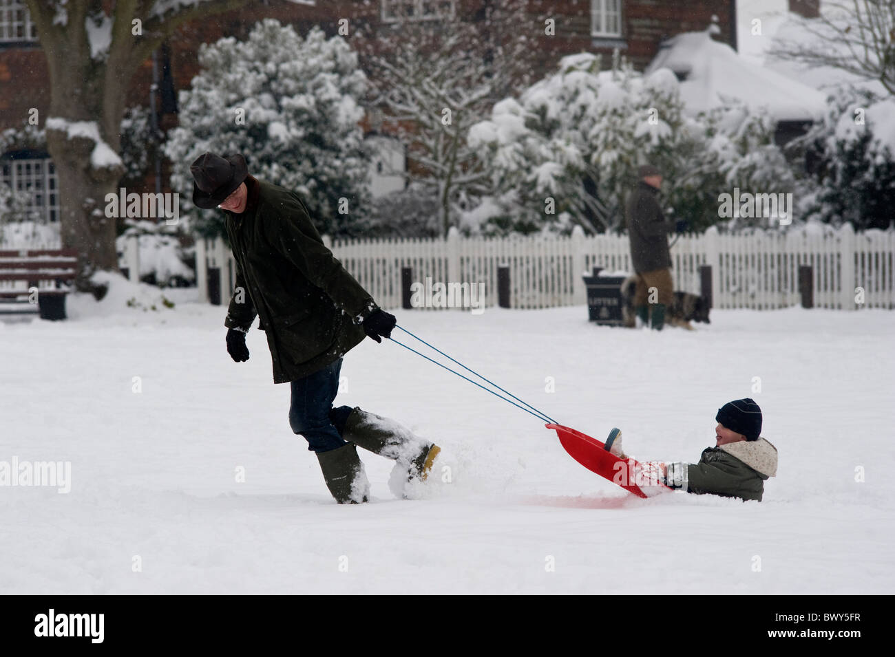 Father playing with son in snow as England is hit by the worst storm in decades. Time to catch up on important family - Stock Image