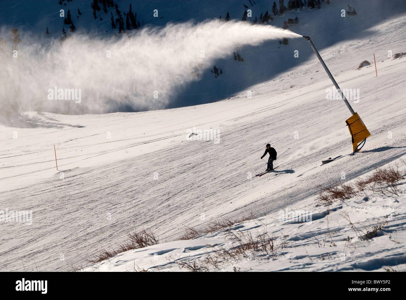 Snowmaking Machine and Downhill skier on Elk Ridge Run Snow Basin Ski Resort Utah USA - Stock Image
