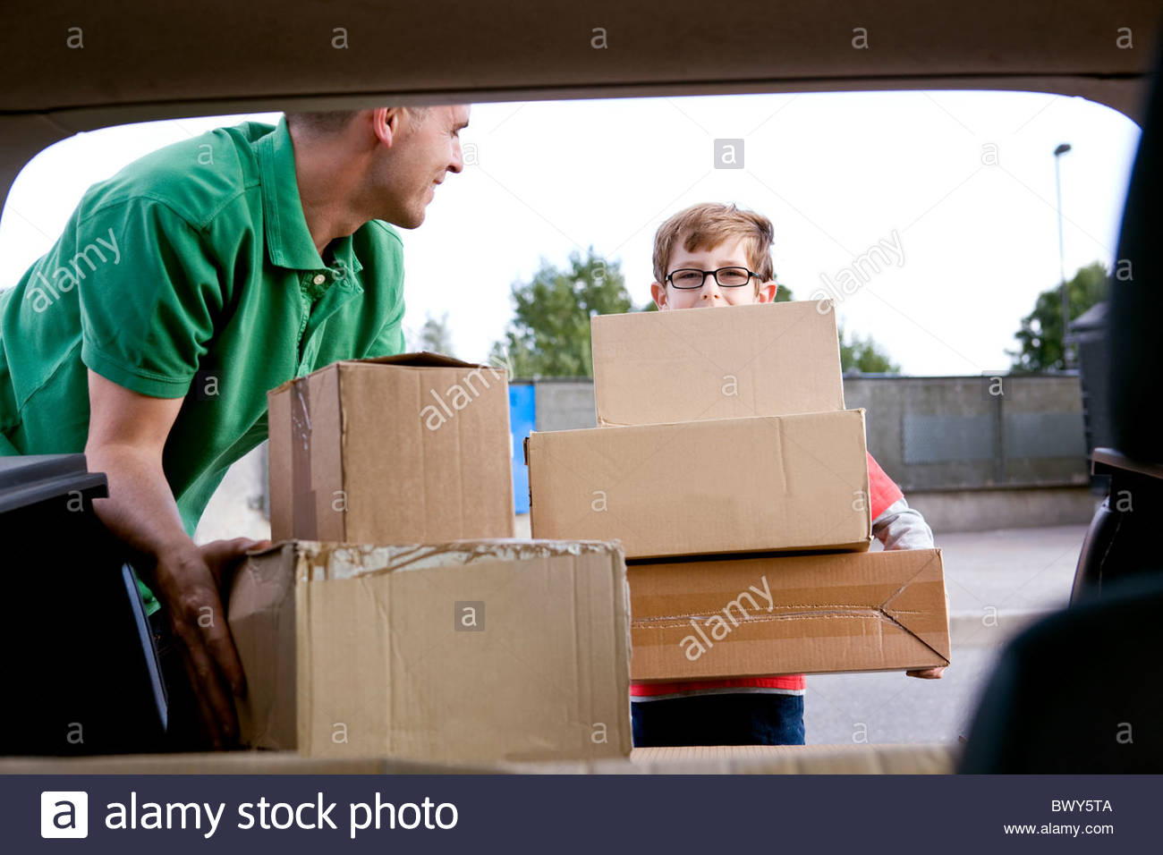 A son helping his father recycle cardboard boxes - Stock Image