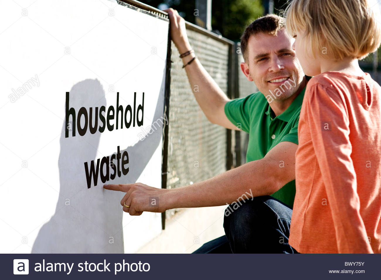 A father teaching his daughter about recycling - Stock Image