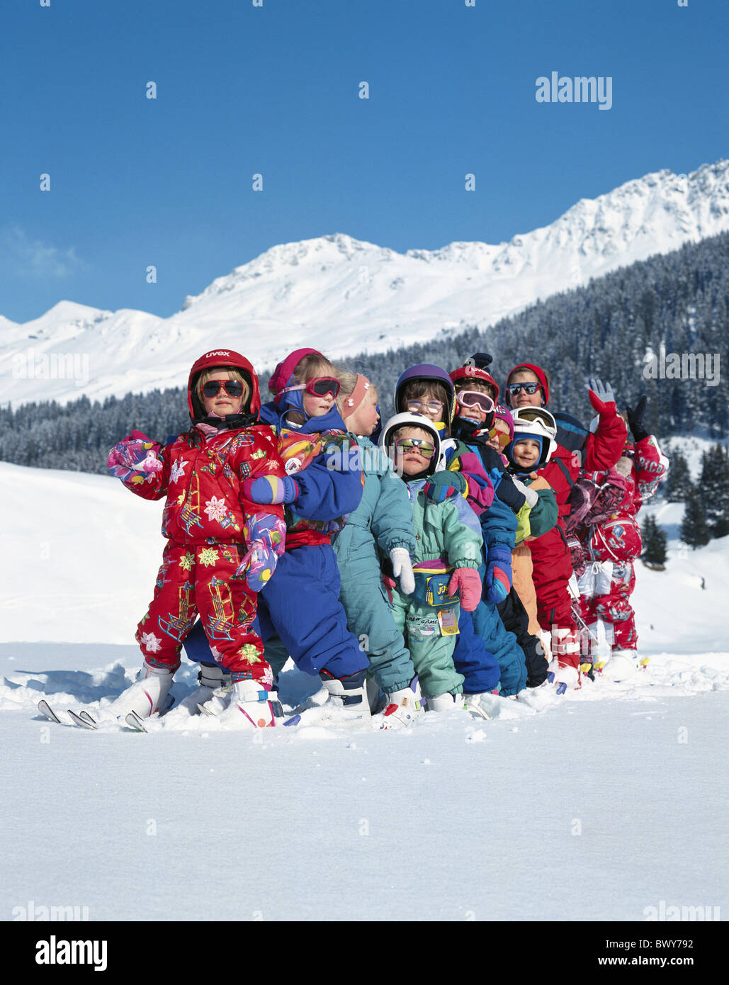 helmets one after other canton Graubunden Grisons Switzerland Europe children row Switzerland Europe skii - Stock Image