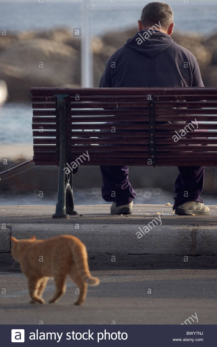 Person sitting bench greece Stock Photo