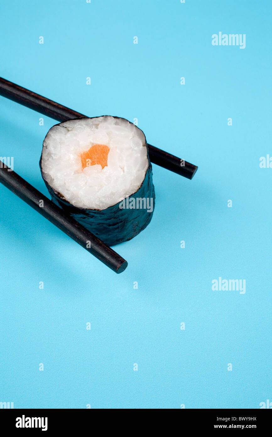 sushi with chop sticks on cyan background - Stock Image
