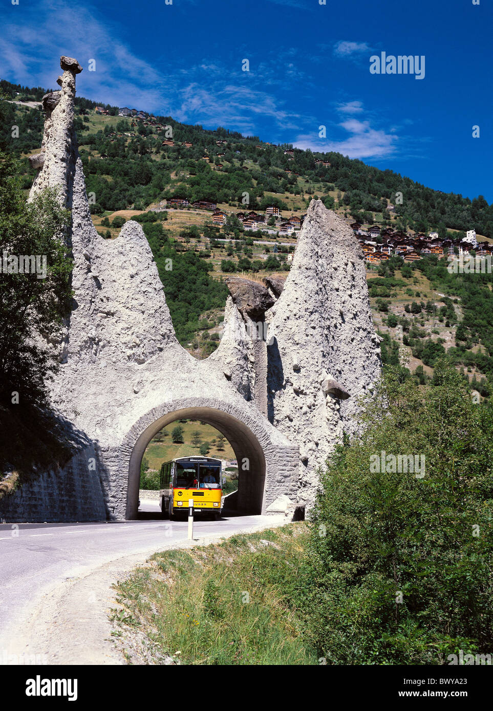 postal car Switzerland Europe Valais Euseigne cliff formations cliff pyramid Pyramides tunnel bus transport - Stock Image