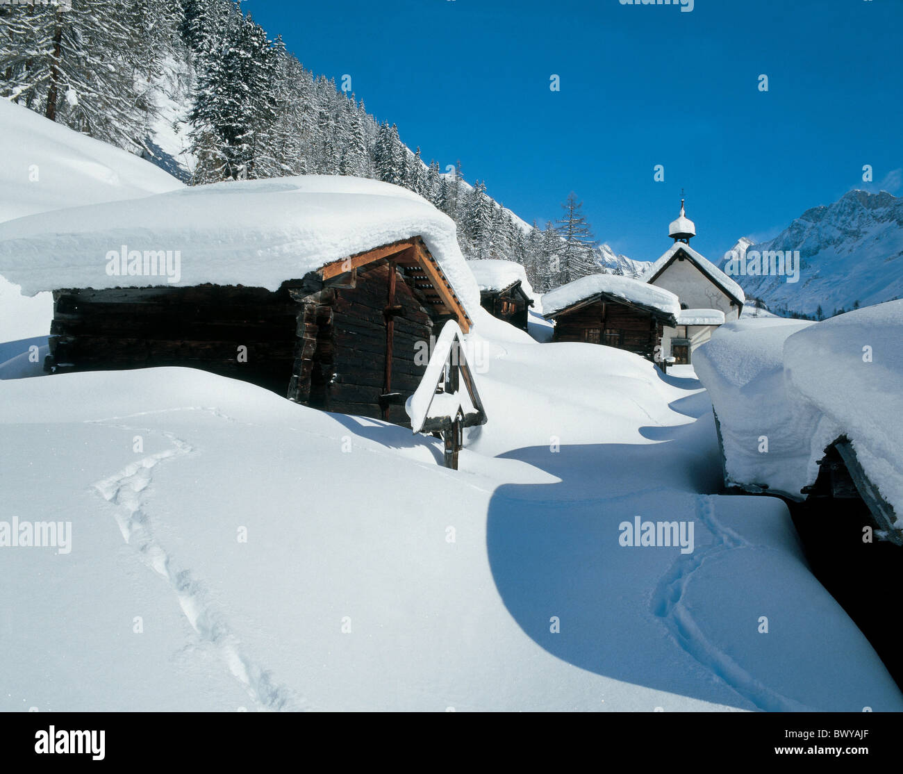 barns Canton Valais chapel cross hamlet Kuhmad Lotschental mountains roadside calvary snow stable village - Stock Image