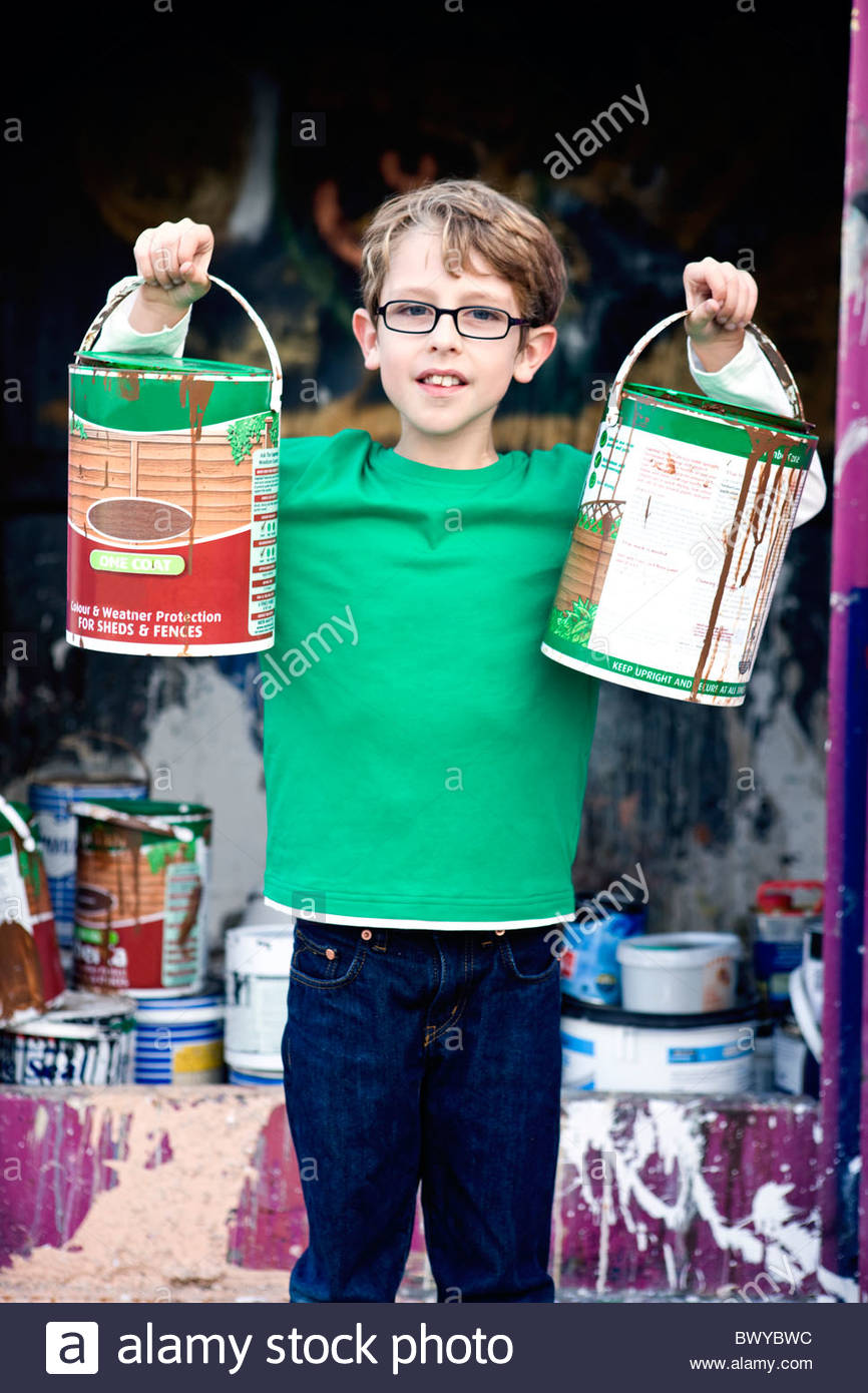 A young boy recycling tins of paint - Stock Image