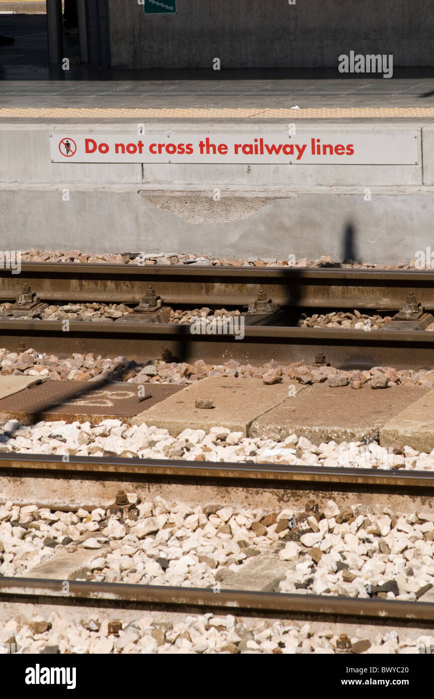 traintracks track tracks line line traintrack station danger signs sign do not cross the crossing station stations - Stock Image