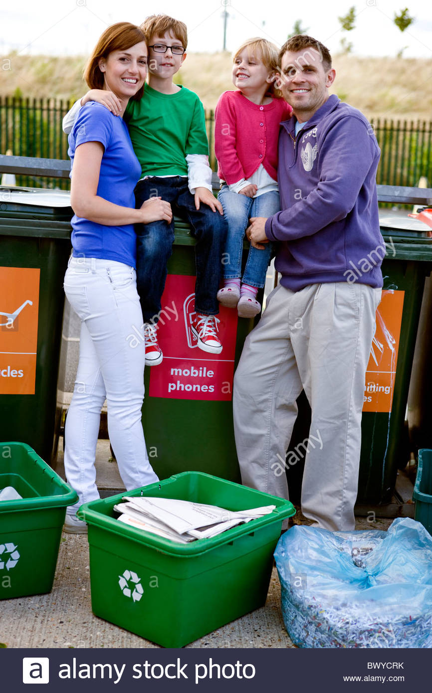 A family standing next to recycling bins Stock Photo