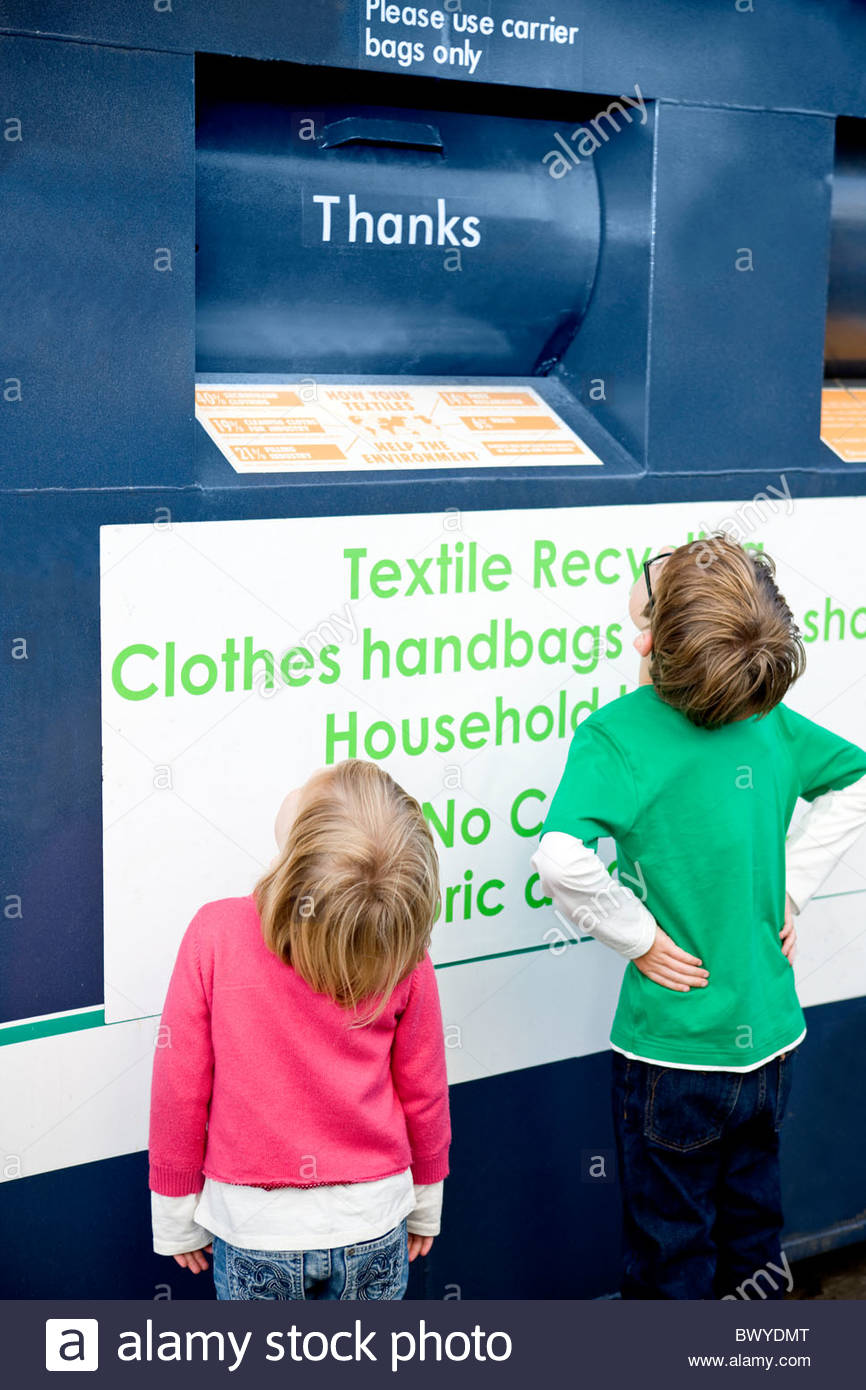 Two young children looking at a recycling container for textiles - Stock Image