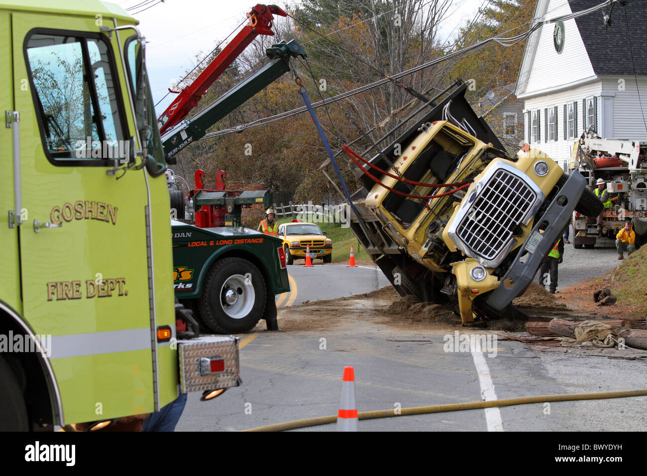 Dumptruck overturned in a traffic accident, emergency personnel responding to the accident scene, uprighting overturned - Stock Image