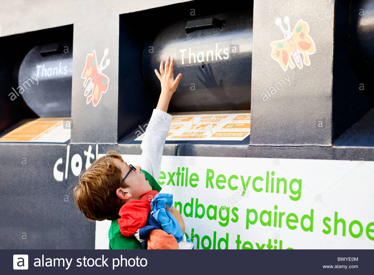 A young boy recycling clothes - Stock Image