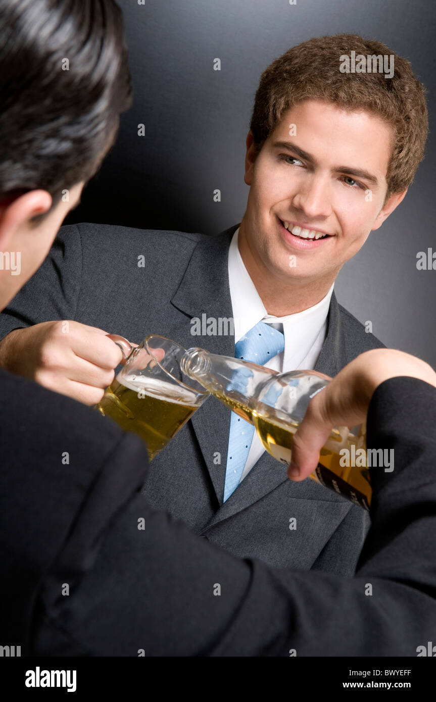 Businessmen toasting with beer - Stock Image