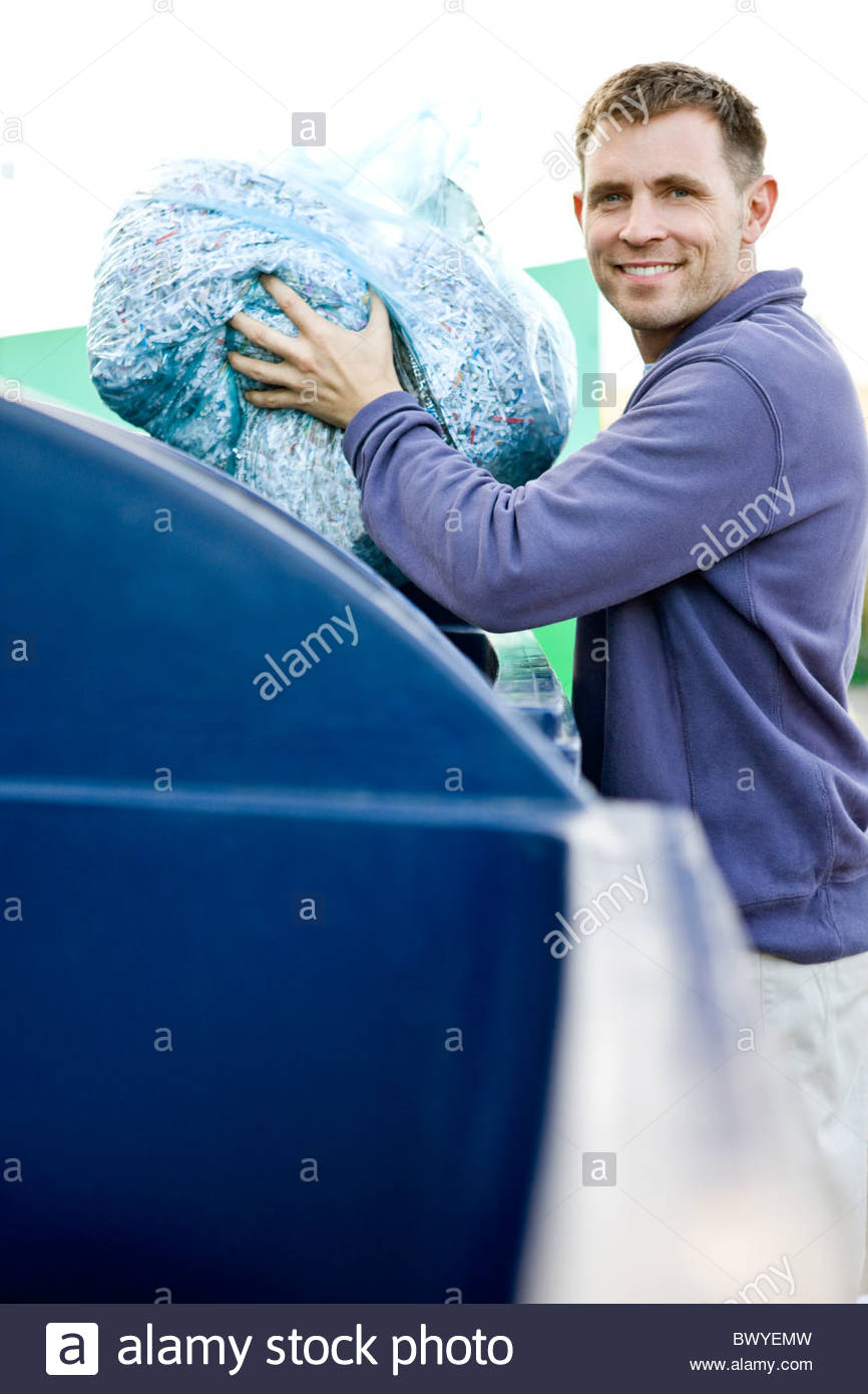 A mid-adult man recycling a bag of shredded paper - Stock Image