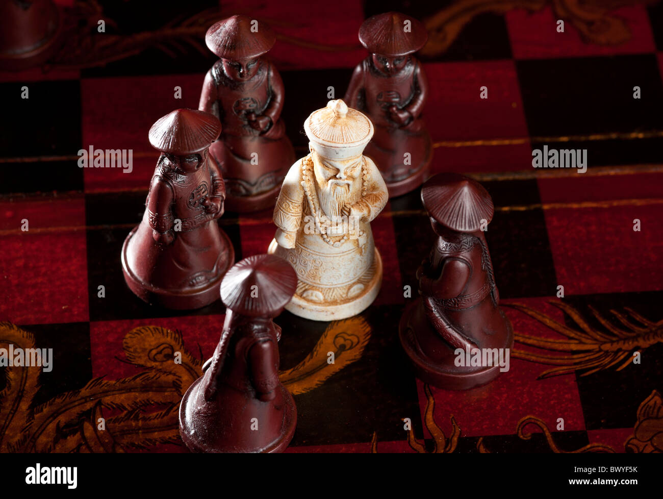 Strategy Game - White Bishop surrounded by Pawn - Stock Image