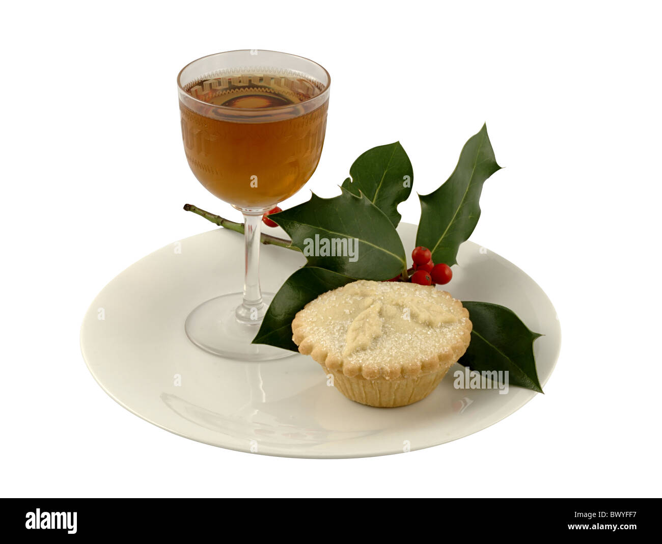 A Christmas mince pie with a glass of sherry and a sprig of holly - Stock Image