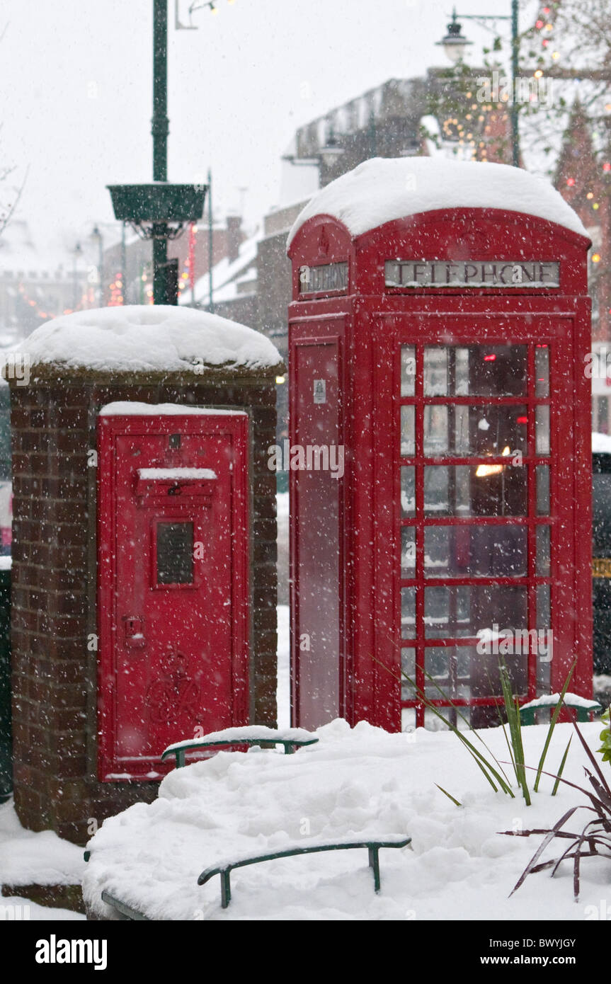 Red telephone box and letter box during snow - Stock Image