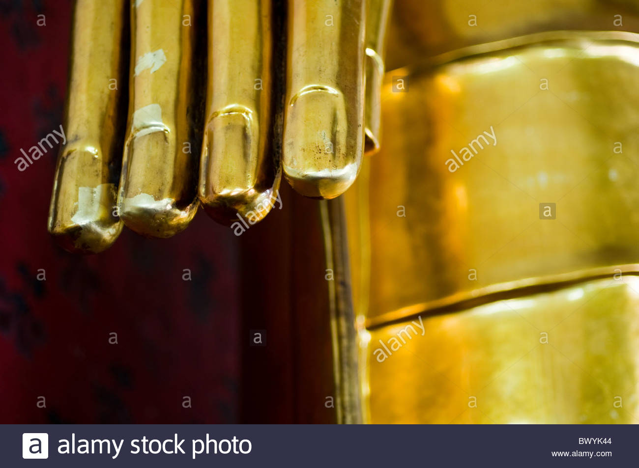 Thailand Buddhism - a close up view of the gold leaf covered fingers of a Buddha in Bangkok Thailand South East Stock Photo