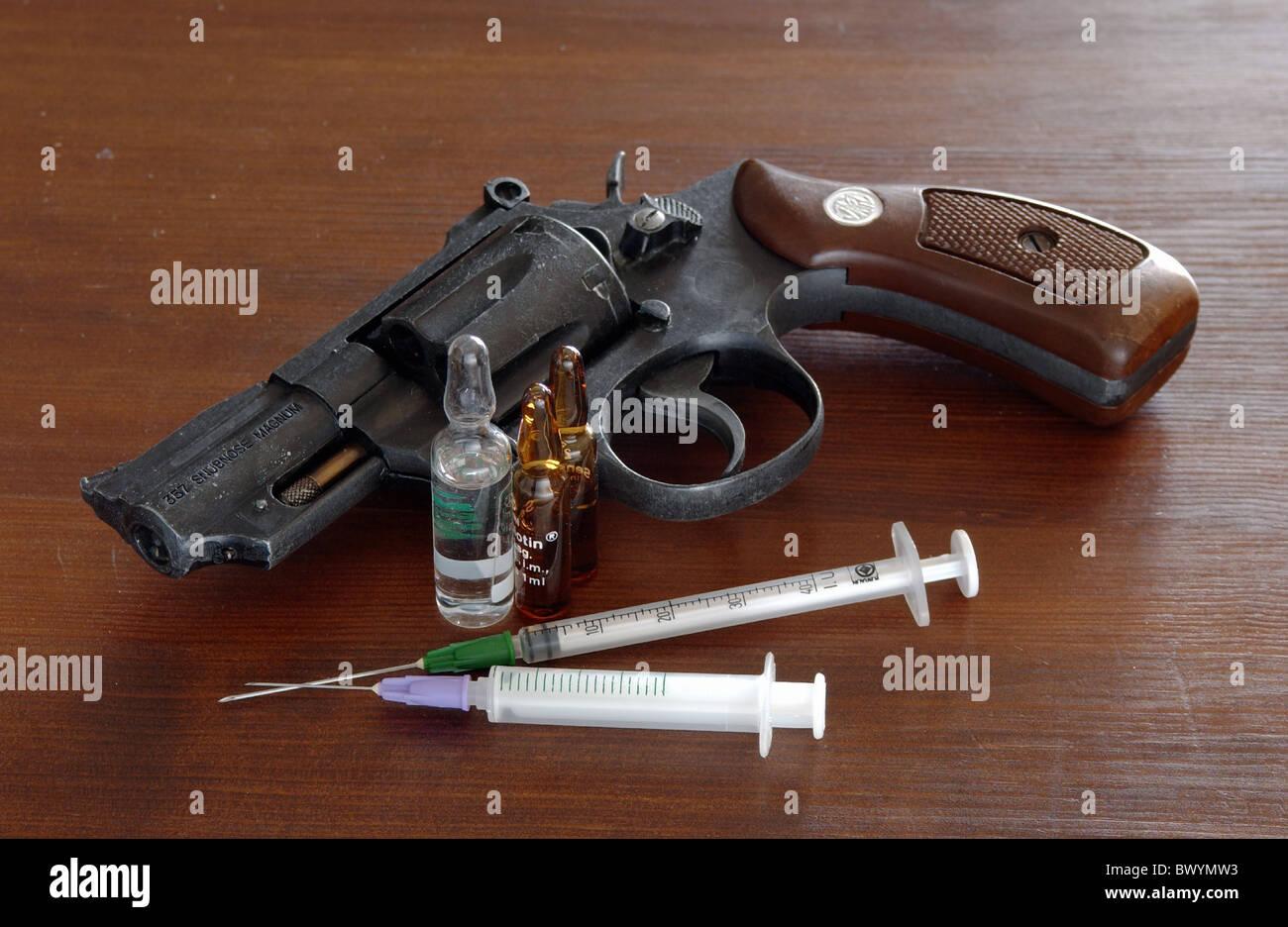 addiction ampoules crime criminal dealers drugs pistol revolver symbol syringes - Stock Image