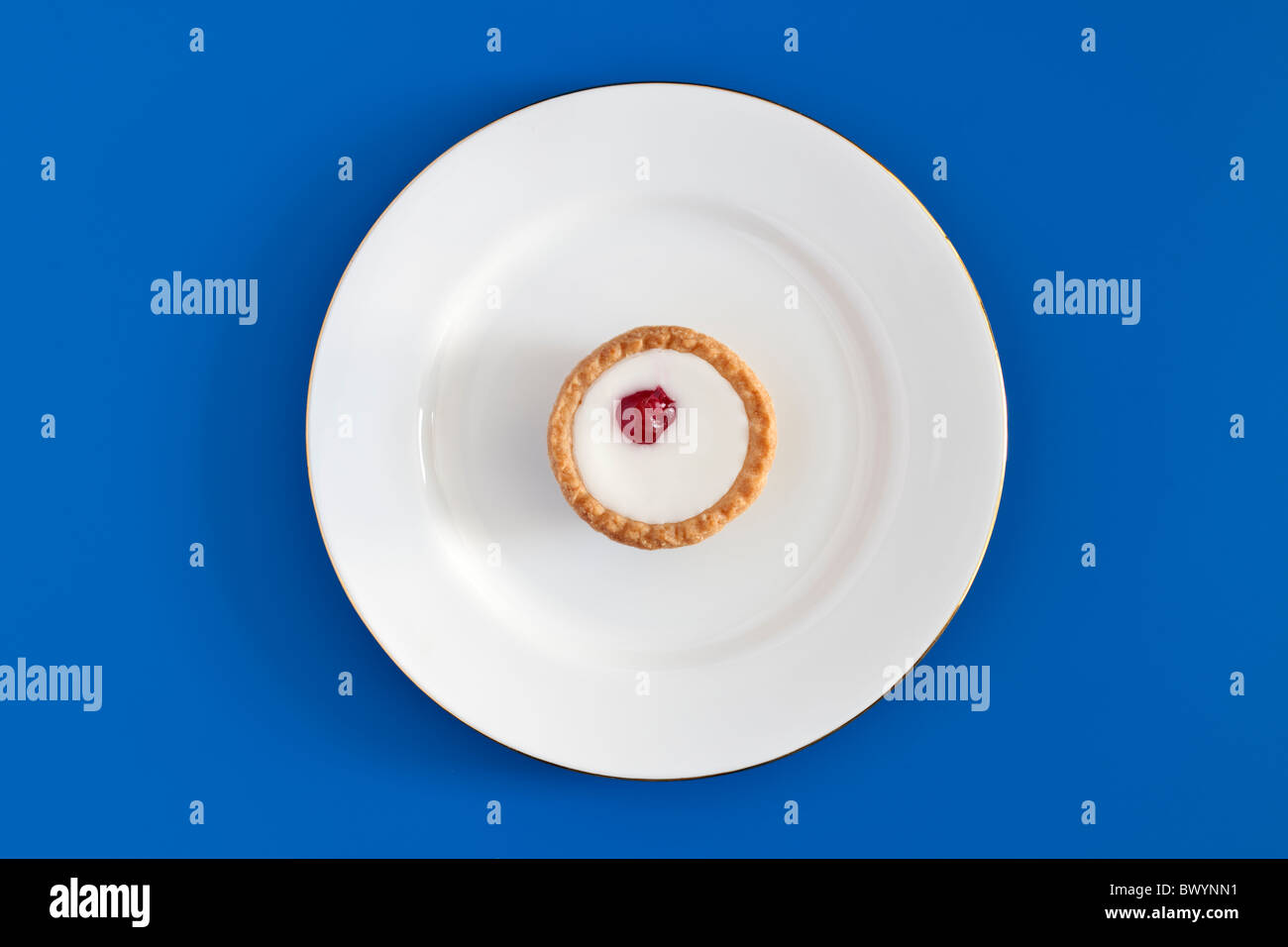 Solitary bakewell bun on a white plate - Stock Image