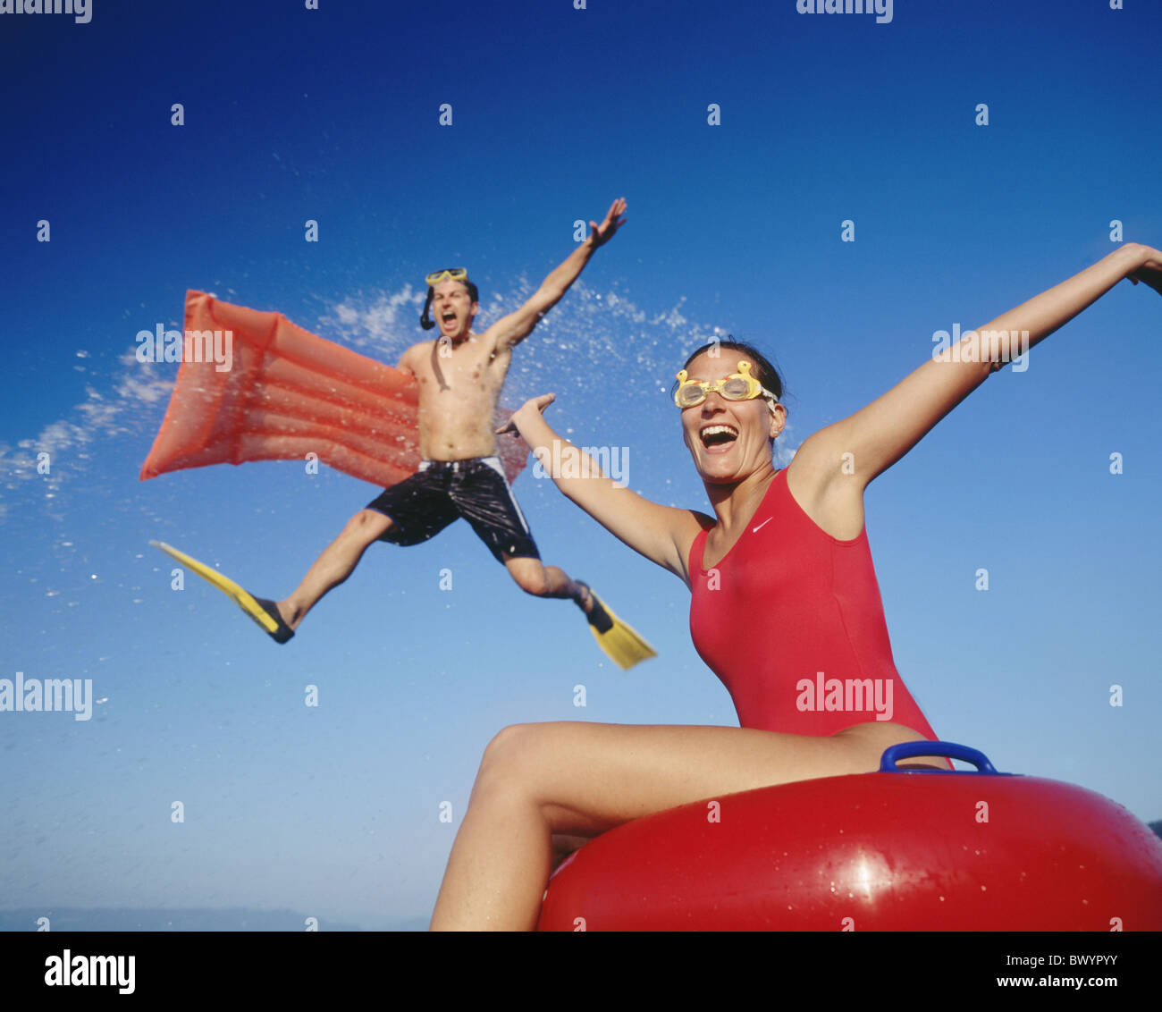 action bathing holidays spare time air bed pair couple splashing swimming floatation swimming help splash - Stock Image