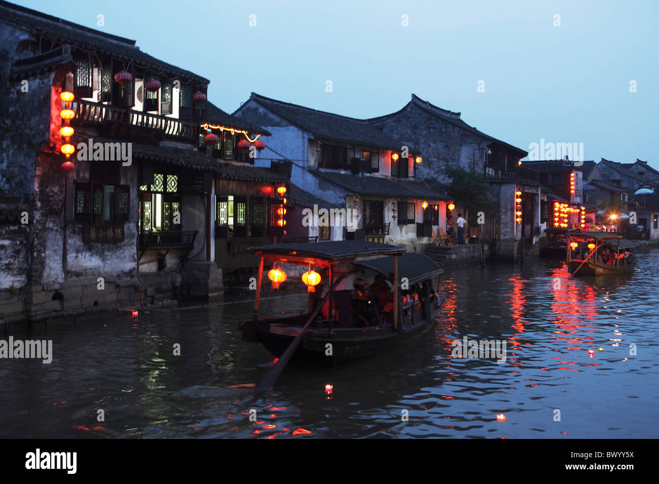 Traditional two story houses along the river at dusk, Xitang, Jiaxing, Zhejiang Province, China - Stock Image