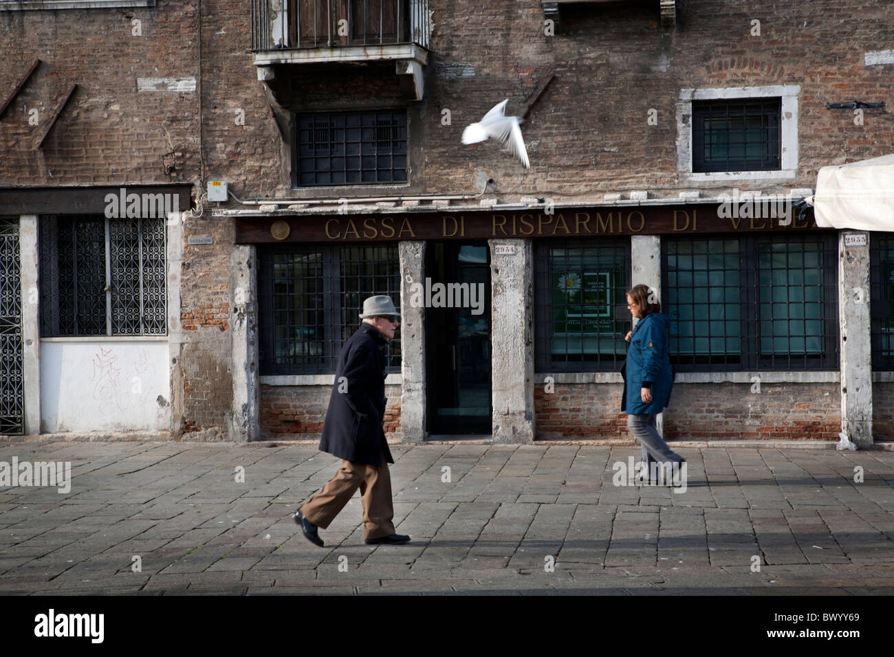 Locals passing by a historic house in the Campo Santa Margherita in Venice. - Stock Image