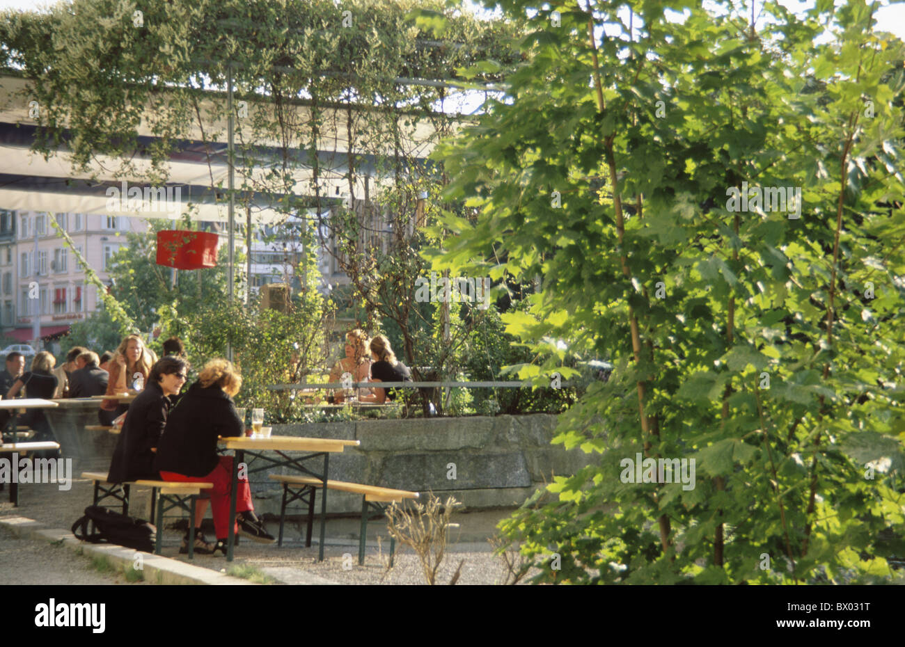 benches El Local garden restaurant guests company cosily restaurant Switzerland Europe tables desks under - Stock Image