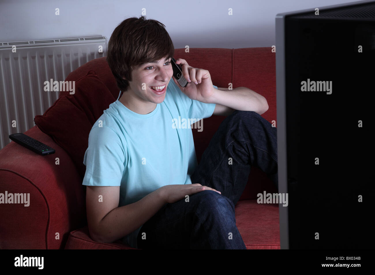 Young male holding a phone smiling and watching tv Stock Photo