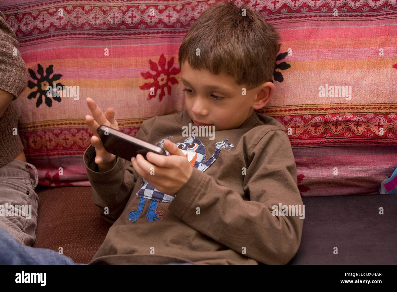 Seven year old boy plays a game on his dad's iPhone. - Stock Image