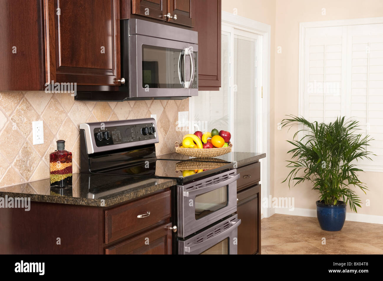 A small modern kitchen with stainless steel appliances, modern cabinetry and beautiful shutters remodeled to an Stock Photo