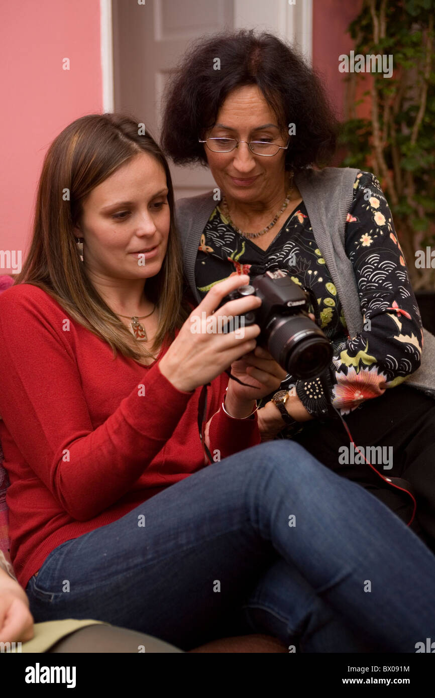 Young woman shows her photo album to her aunt that is stored on her digital camera. Both are Polish immigrants in - Stock Image