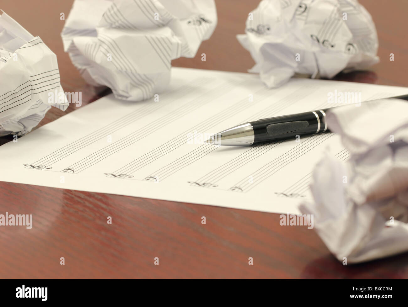 Writer's Block - Blank staff paper, mechanical pencil, and crumbled balls of paper scattered on a wooden desk. - Stock Image