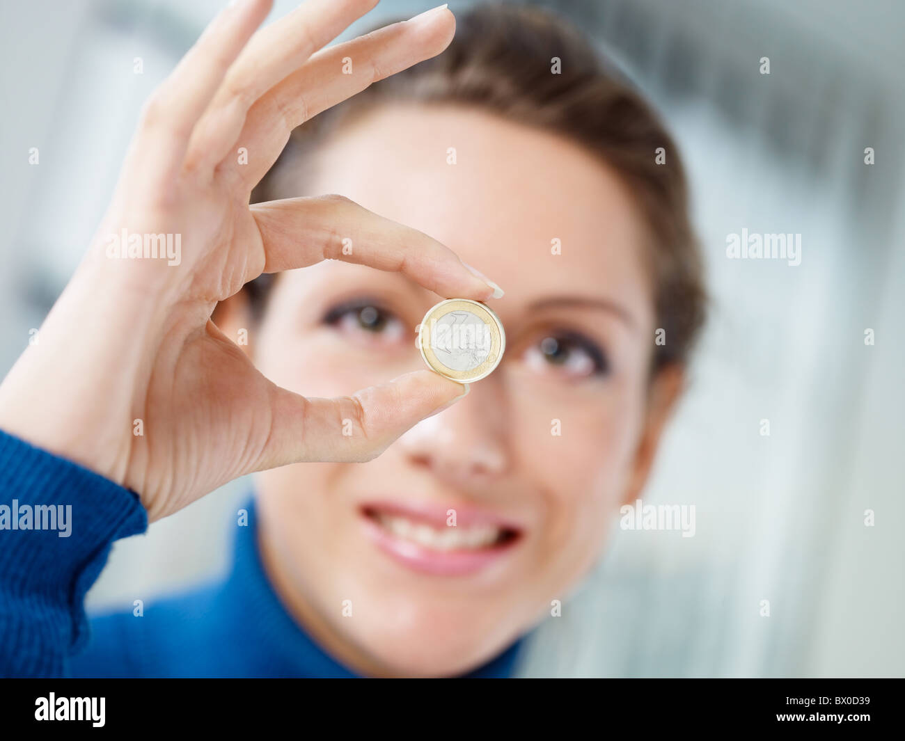 woman holding one euro coin - Stock Image