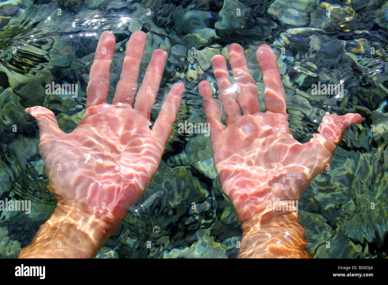 hands underwater river water wavy distorted shapes - Stock Image