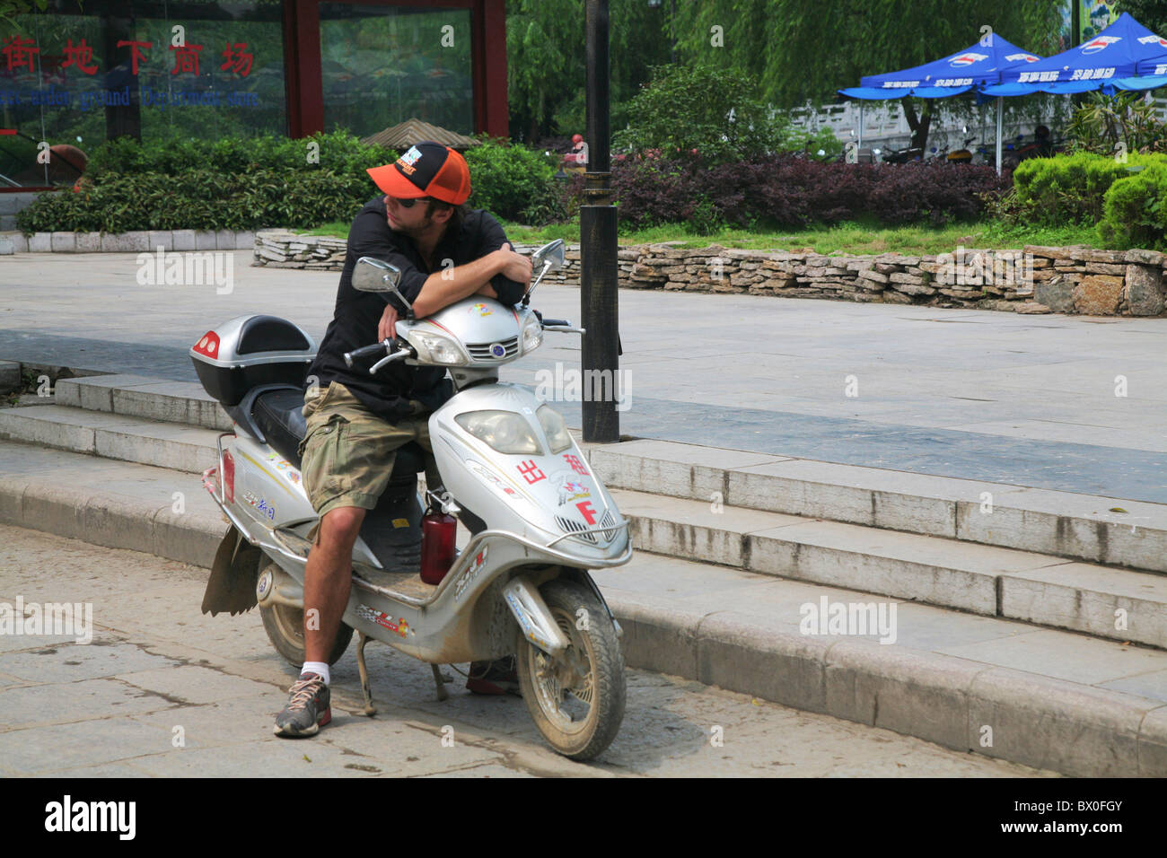Caucasian tourist on a rented motorcycle, West Street, Yangshuo, Guilin, Guangxi Province, China - Stock Image