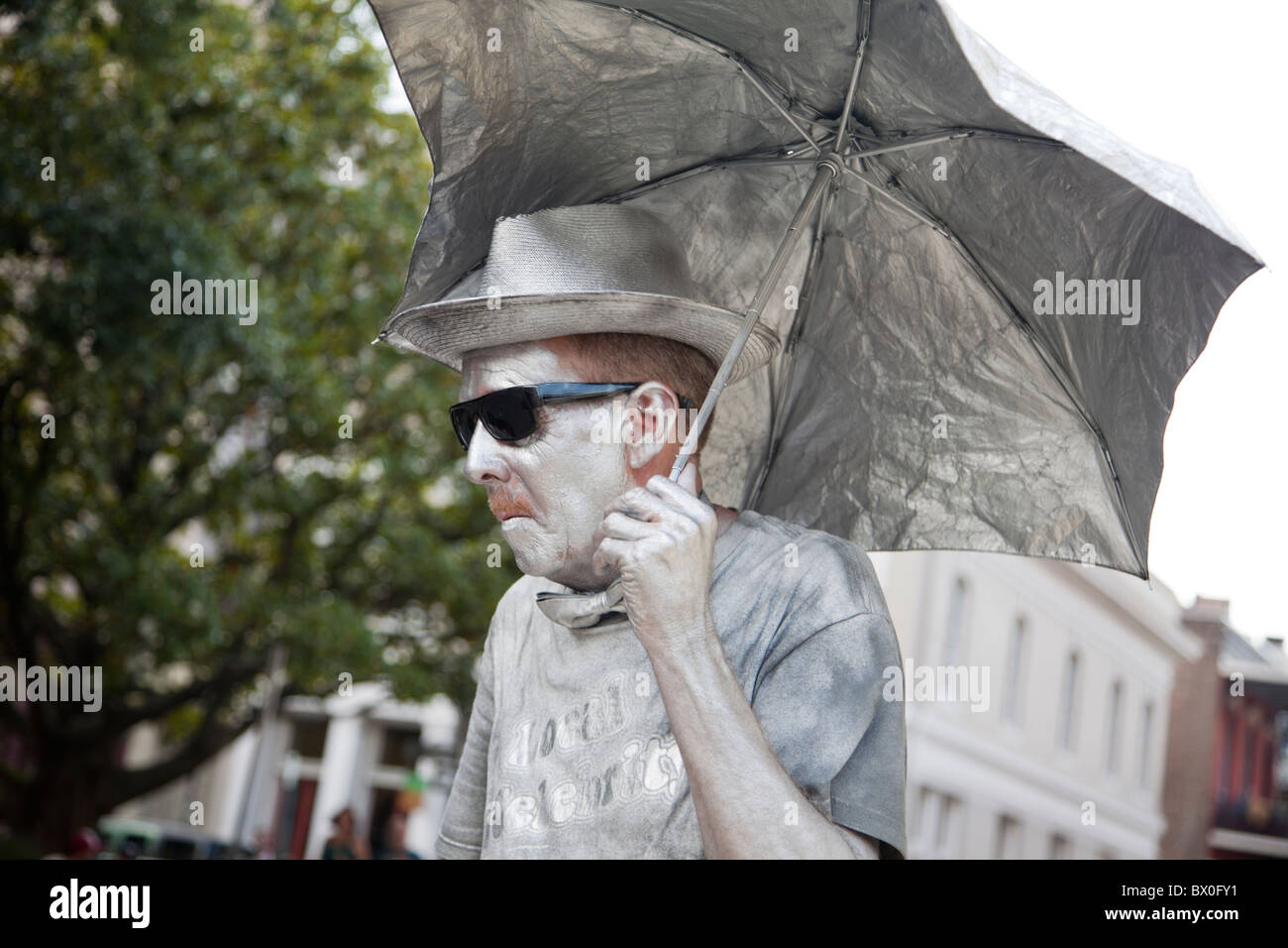 A man, painted in silver and standing still as a statue, performs for tips in New Orleans, Louisiana. - Stock Image