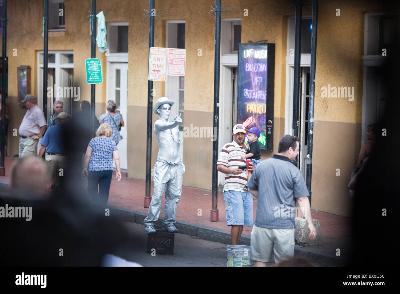 Mimes/performers painted in silver and gold pose for tips on Bourbon Street in New Orleans, Louisiana's French - Stock Image