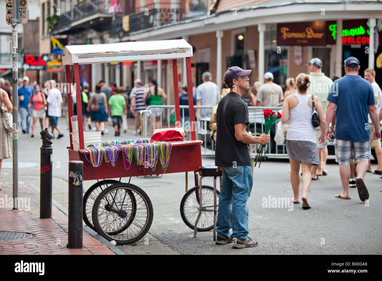 A man sells Mardi Gras beads on Bourbon Street in New Orleans, Louisiana's French Quarter. - Stock Image