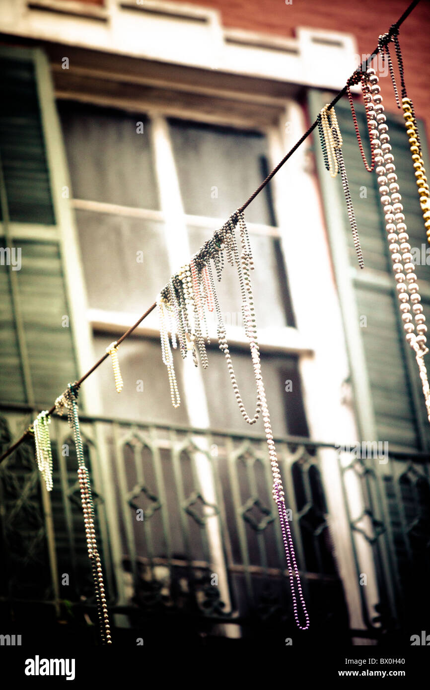 Mardi Gras beads hang on electrical/telephone wires and residents' balconies throughout the French Quarter in - Stock Image