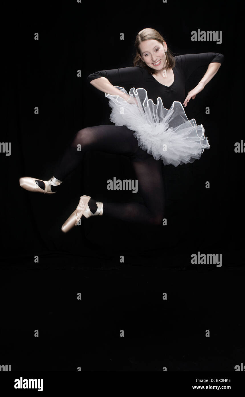 A teenage ballerina wearing black tights and white tutu jumps in the air clicking her heals Stock Photo