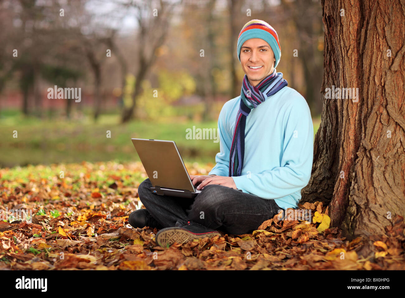 Young man with hat and scarf working on laptop - Stock Image