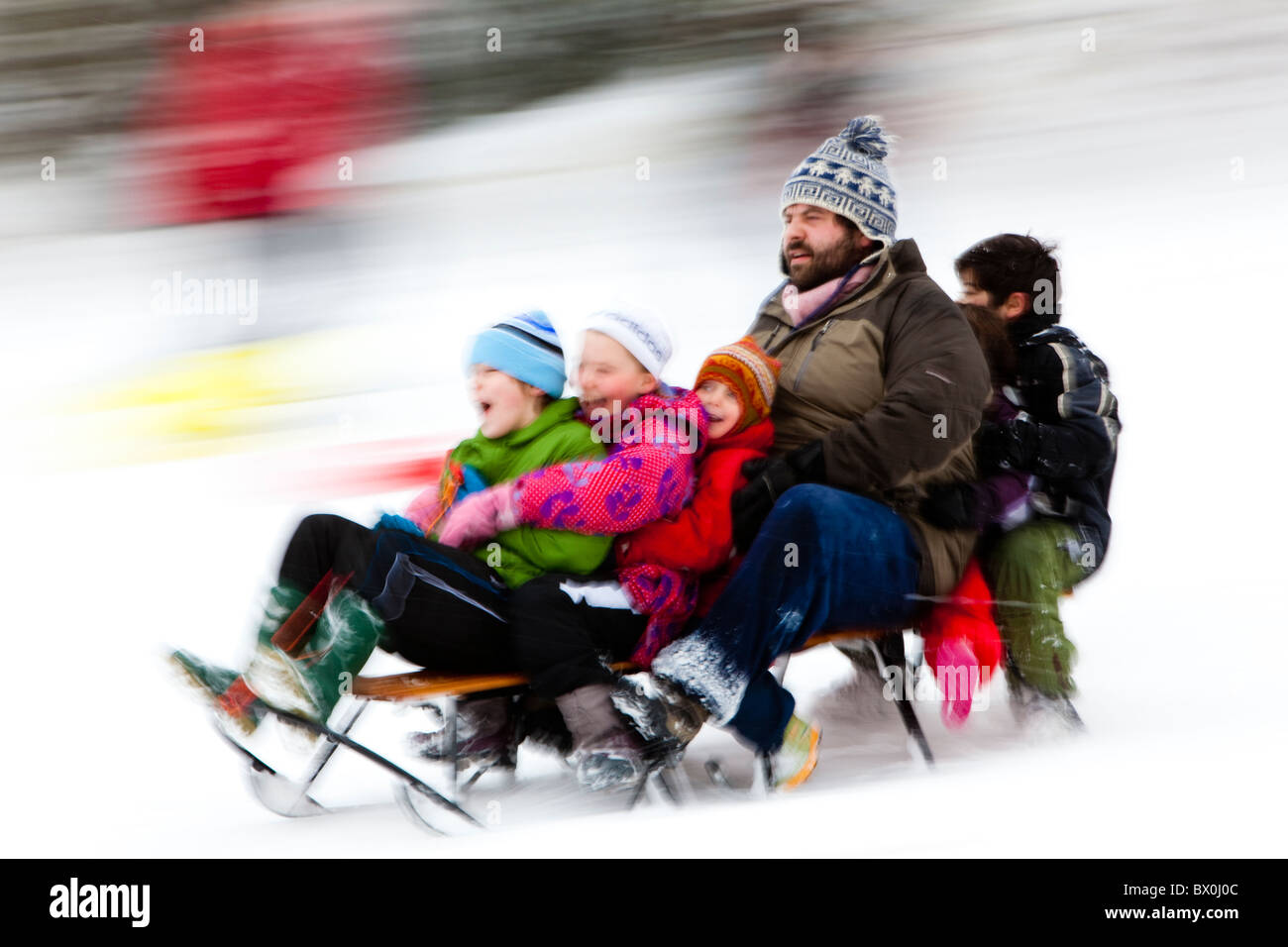 Family fun on a sledge, Kent, UK, winter - Stock Image