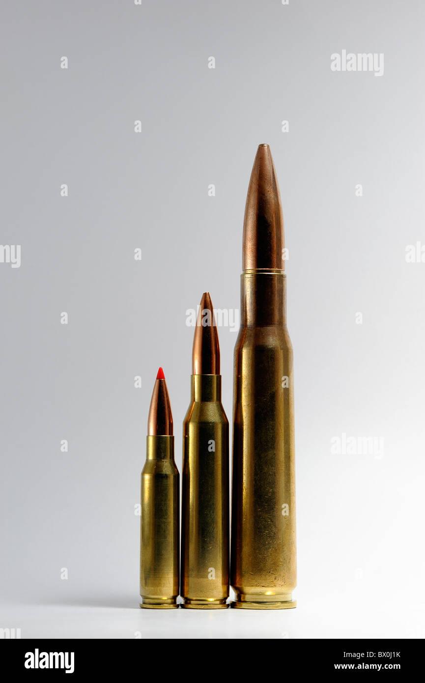 Range of rifle cartridges calibre 308 Winchester, 338 Lapua Magnum and 50 Browning Machine Gun against a plain white - Stock Image