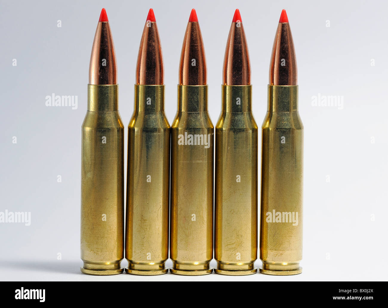 A line of five 308 Winchester rifle cartridges against a plain white background - Stock Image