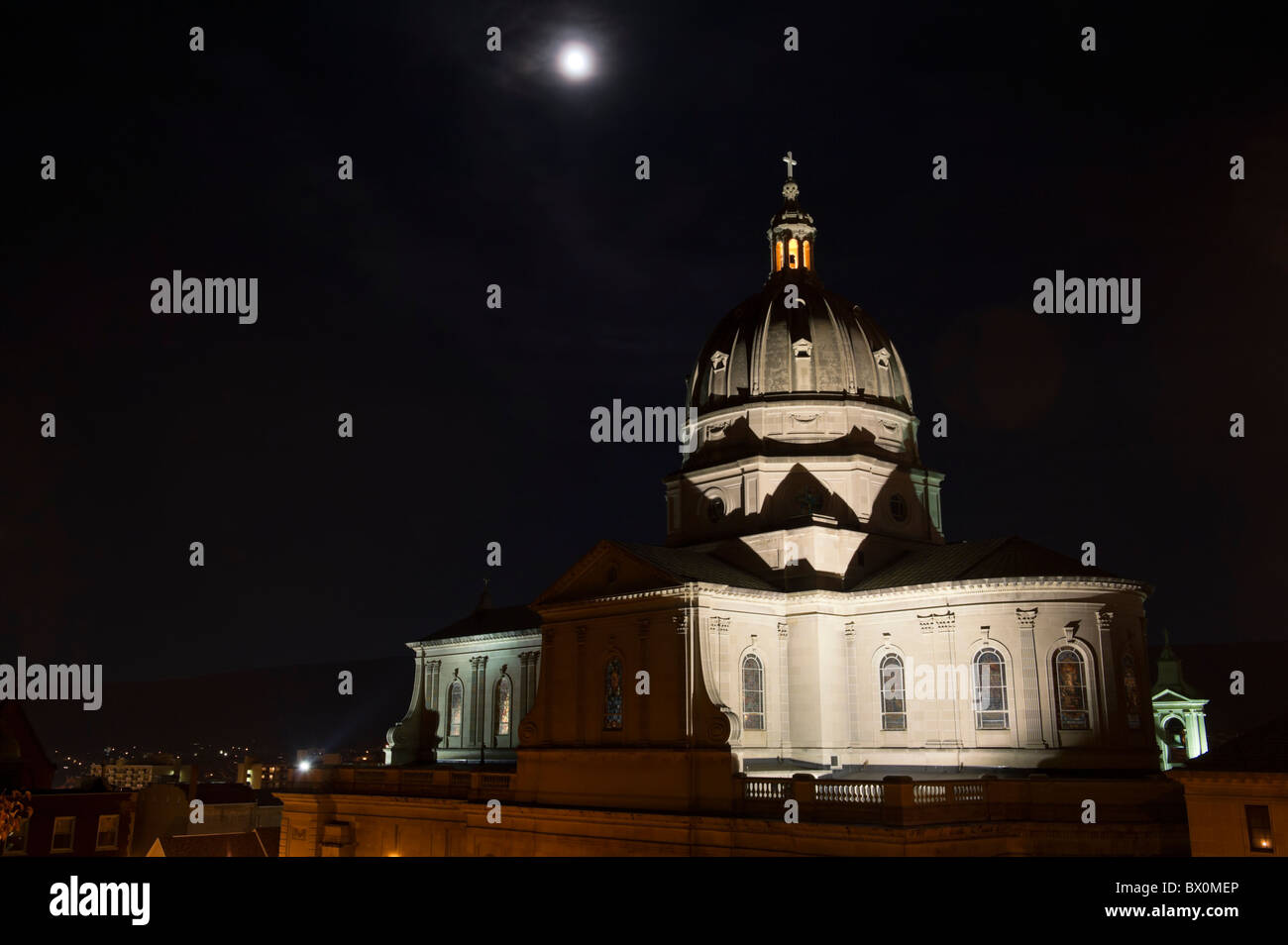 Cathedral church dome under full moon, photographed at night with rotunda and cross lit, Altoona, PA, USA. - Stock Image