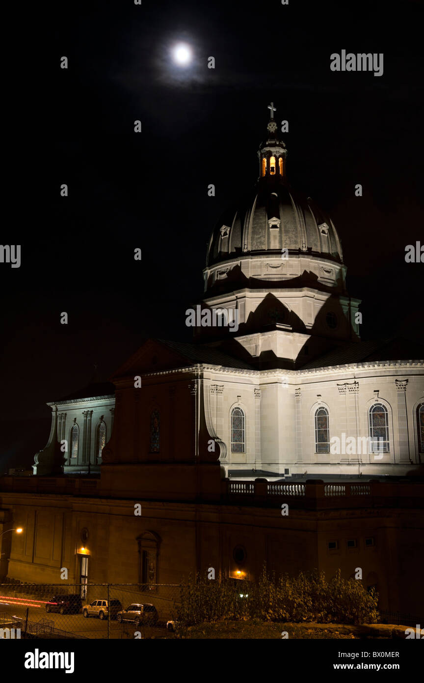 Cathedral church dome under full moon, photographed at night with top tower lit, Altoona, PA, USA. - Stock Image